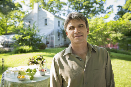 On The Farm. A Man In A Farmhouse Garden, Beside A Round Table With Fresh Lemonade Drinks.