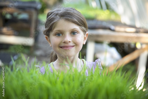 On The Farm. A Girl Standing Smiling By A Glasshouse Bench Looking Over The Green Shoots Of Seedlings Growing In Trays.