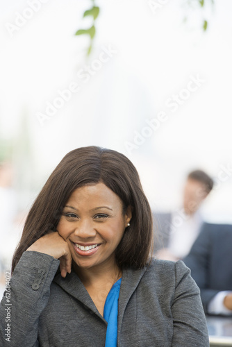 Summer. A Woman In A Grey Suit With A Bright Blue Shirt Smiling.