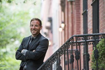Business People. A Man In A Suit On The Steps Of A Brownstone Building. Arms Folded.