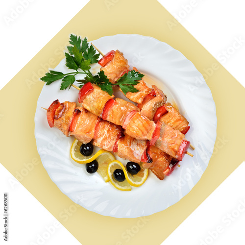 Dish of salmon fish on skewer on white plate.