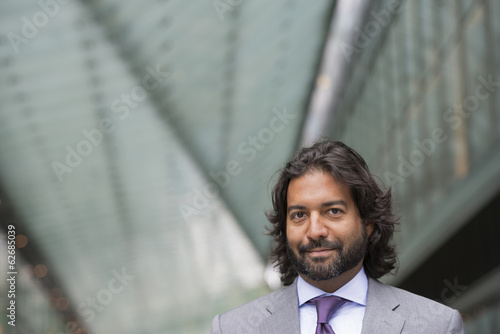 Business People. A Man In A Business Suit With A Full Beard And Curly Hair.