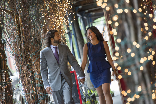 Business People. Two People, A Man And Woman Holding Hands And Walking Under A Pergola, Lit With Fairy Lights.