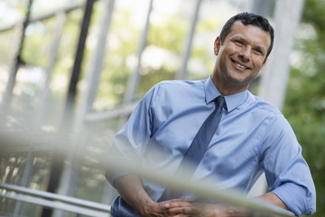 Business People Outdoors. A Latino Businessman In Shirt And Tie, Leaning On A Railing. Relaxing.