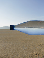 The Landscape Of The Black Rock Desert In Nevada. A Bottle Of Water. Filtered Mineral Water. Sideways. The Water Level Matching The Horizon.