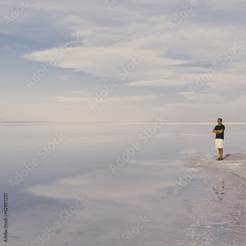 A Man Standing At Edge Of The Flooded Bonneville Salt Flats At Dusk. Arms Folded.