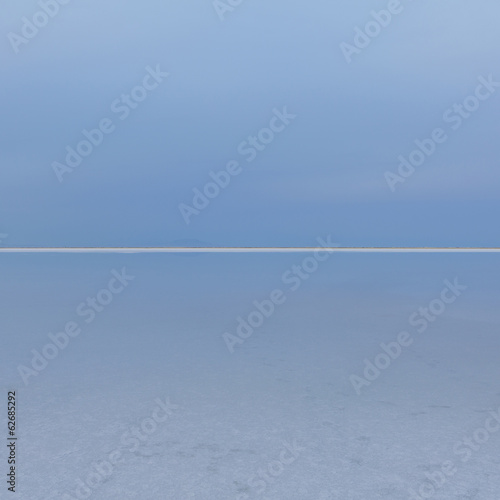 Shallow Water Over The Surface At The Bonneville Salt Flats Near Wendover, At Dusk. The Land Meeting The Sky On The Horizon, And A White Line Of Salt Crystals.