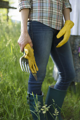 Organic Farm. A Worker Wearing Blue Jeans, Yellow Thick Gardening Gloves Holding A Trowel.