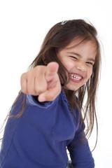 enfant pointe du doigt avec sourire malicieux