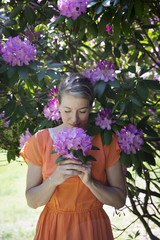 A Woman In An Orange Summer Dress Standing Under A Shrub, Holding A Large Purple Flowerhead.