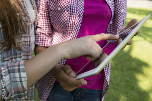 Two Girls Sitting Outdoors On A Bench, Using A Digital Tablet. Close Up Of Their Hands Touching The Screen.
