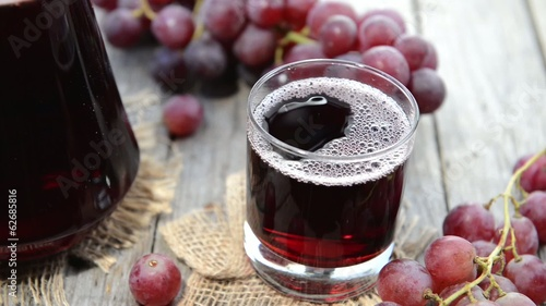 Fresh made Grape Juice in a glass (wooden background)