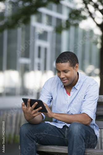 Summer. A Man Sitting On A Bench Using A Digital Tablet.