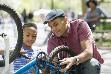 A Family In The Park On A Sunny Day. A Father And Son Repairing A Bicycle.
