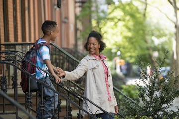 A Mother And Son, A Woman And A Boy On A Flight Of Steps Outside A Brownstone Building.