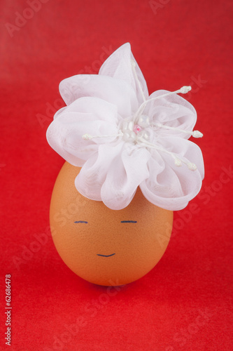 Toy egg girl with white artificial flower - on red background