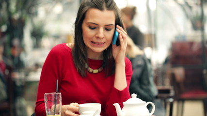 Young attractive woman talking on cellphone in cafe