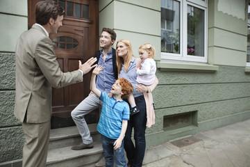 Deutschland, Düsseldorf, Junge, high Five, Immobilienmakler und Familie stehen im Hintergrund