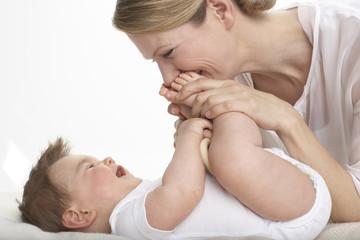 Mutter küssen die Füße des lächelnden Babys
