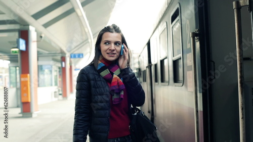 Young woman talking on cellphone on train station
