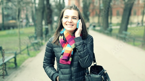 Young woman talking on cellphone in city park