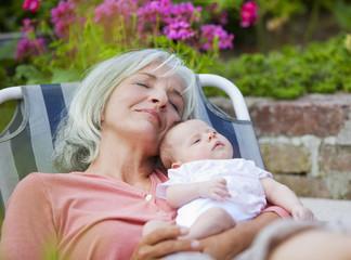 Deutschland, Bayern, Frau mit Enkelkind Entspannung im Liegestuhl