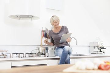 Deutschland, München, Frau beobachtet Tablet PC und die Zubereitung von Speisen