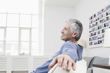 Deutschland, München, Senior sitzt auf der Couch