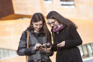 Zwei junge Frauen mit Tablet PC im Freien