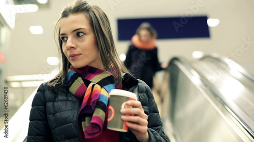 Woman on escalator drinking coffee