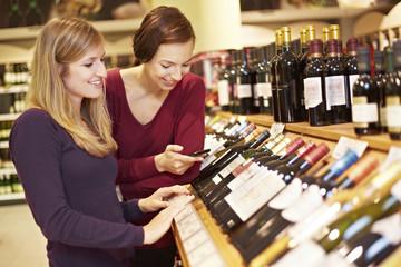 Deutschland, Köln, Junge Frauen Inspektion Wein im Supermarkt