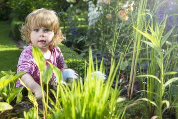 Deutschland, NRW, Baby, spielen in der Nähe von Gartenteich