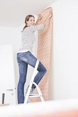 Frau klebt die Tapete an der Wand