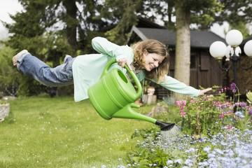 Deutschland, Bayern, Kaufbeuren, Frau mittleren Alters, gießen von Pflanzen im Garten