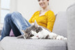 Deutschland, München, Frau mit Katze auf der Couch