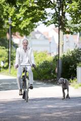 Deutschland, Bayern, Mann auf Fahrrad mit Hund Weimaraner
