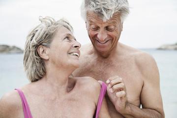Spanien, Senioren Paar am Strand ausziehen