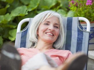 Deutschland, Bayern, Seniorin sitzt im Liegestuhl