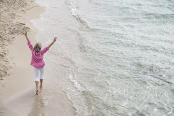 Spanien, Seniorin zu Fuß am Strand