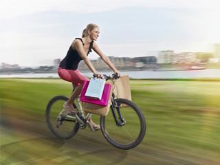 Deutschland, Köln, junge Frau auf dem Fahrrad mit Einkaufstaschen