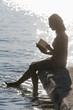 Deutschland, Bayern, Seniorin liest ein Buch am See Stamberg