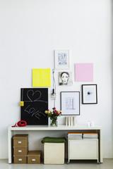 Deutschland, München, Bilderrahmen an der Wand hängen mit Blumenvase und Telefon auf Regal