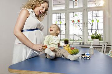 Deutschland, Bonn, Schwangere Mutter, zeigt Früchte dem Sohn im Wohnzimmer