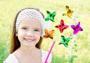 Smiling little girl playing with windmill toy