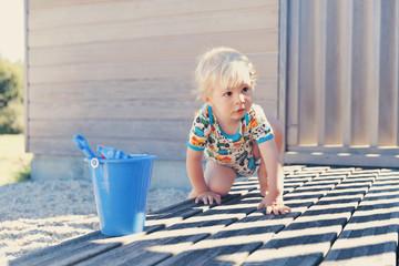 Kleiner Junge hockt auf Terrasse