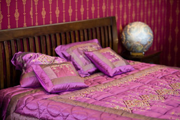 Detail of magenta cushion on the bed