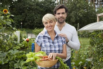 Deutschland, Nürnberg, Senioren Paar mit Gemüse im Garten