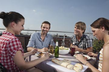 Deutschland, Berlin, Männer und Frauen am Grill auf der Dachterrasse