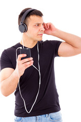 stunned curious man listening something on mobile over headphone