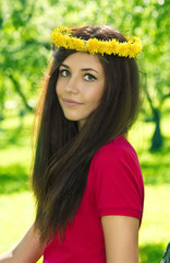 Attractive girl in wreath of dandelion flowers. Spring theme.